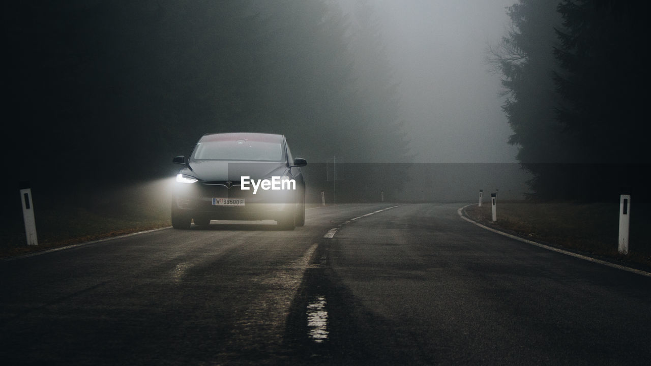 CAR ON ROAD IN FOGGY WEATHER