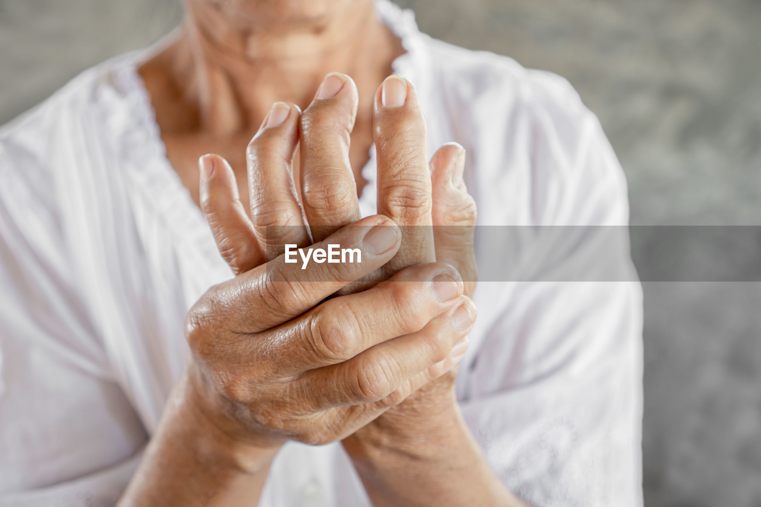 Close-up of senior woman with wrinkled fractured hands