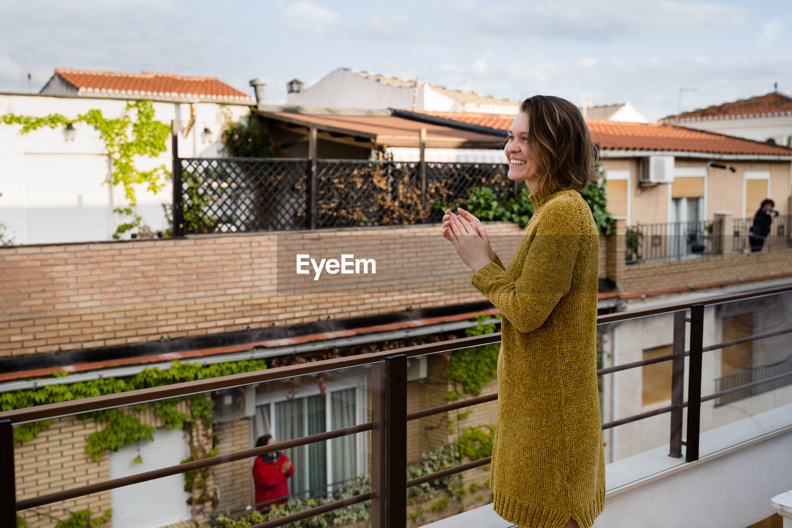 Side view of smiling woman clapping hands while standing by railing in balcony