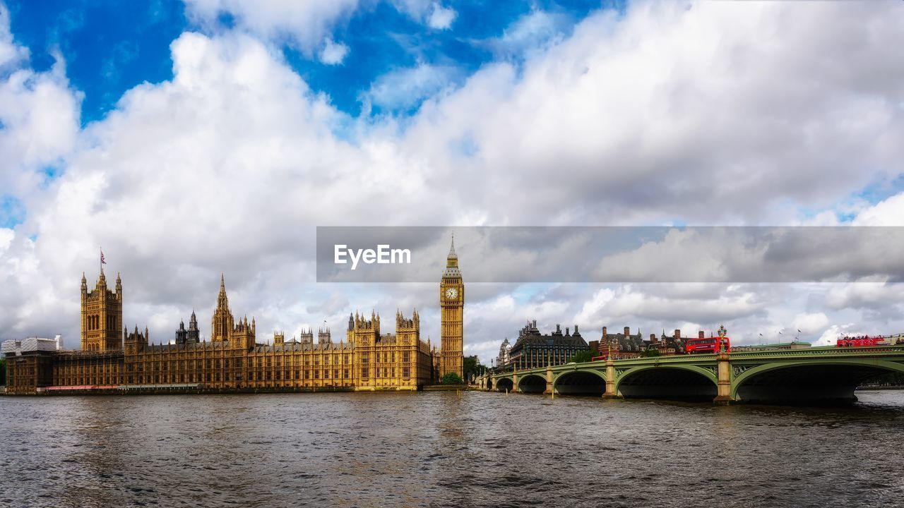 architecture, river, built structure, cloud - sky, clock tower, travel destinations, bridge - man made structure, water, building exterior, connection, sky, waterfront, outdoors, government, no people, city, day