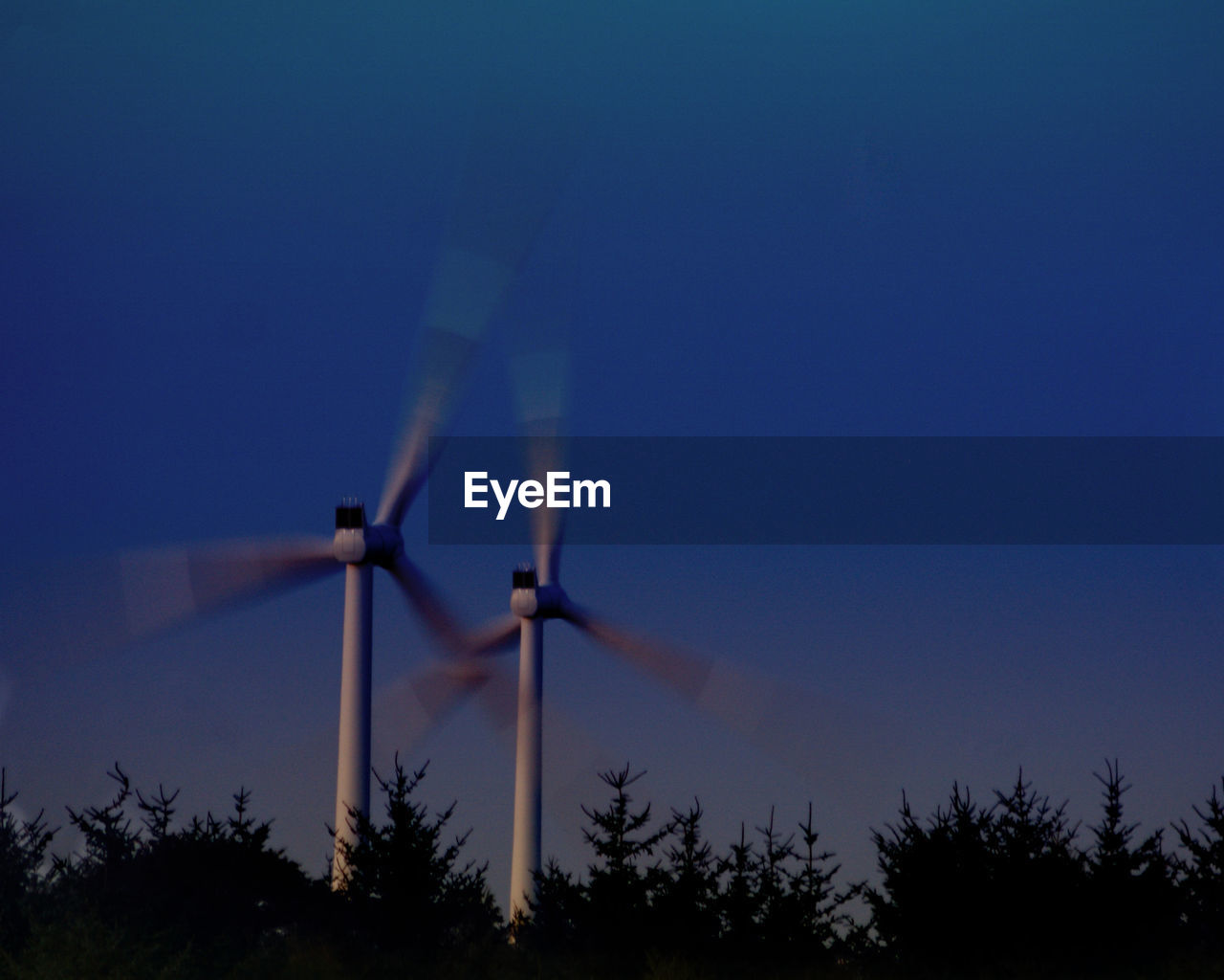 fuel and power generation, sky, environmental conservation, wind turbine, alternative energy, renewable energy, wind power, environment, turbine, tree, nature, plant, technology, blue, low angle view, clear sky, land, no people, outdoors, motion, power in nature, sustainable resources, power supply