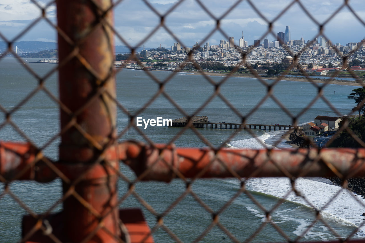 fence, chainlink fence, protection, barrier, boundary, security, metal, safety, sky, water, day, nature, architecture, sea, no people, close-up, built structure, outdoors, transportation