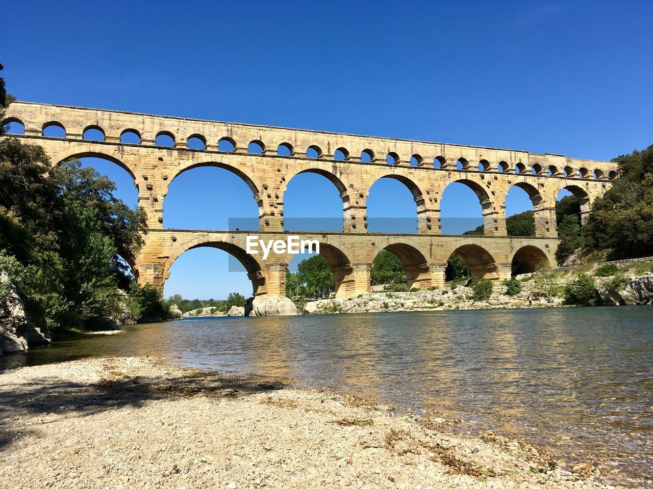 arch, built structure, architecture, water, sky, nature, connection, clear sky, river, day, history, sunlight, blue, bridge, no people, the past, bridge - man made structure, tree, travel destinations, outdoors, arch bridge, arched, ancient