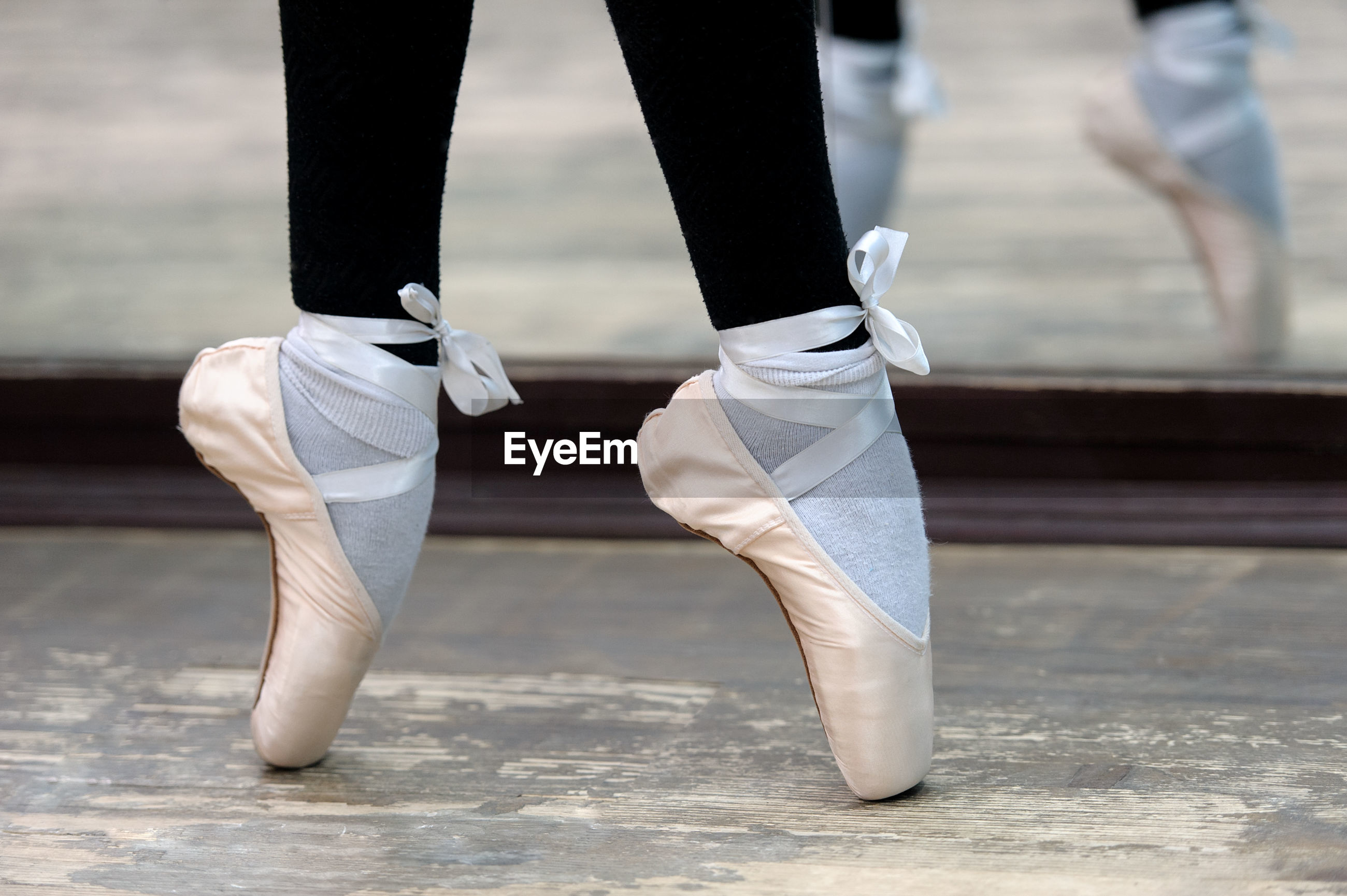 Low section of ballerina tiptoeing on hardwood floor