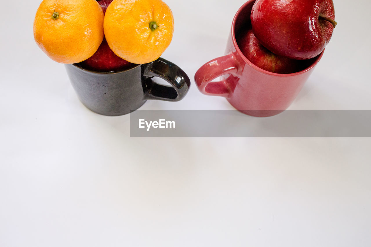 High Angle View Of Cups With Fruits Over White Background