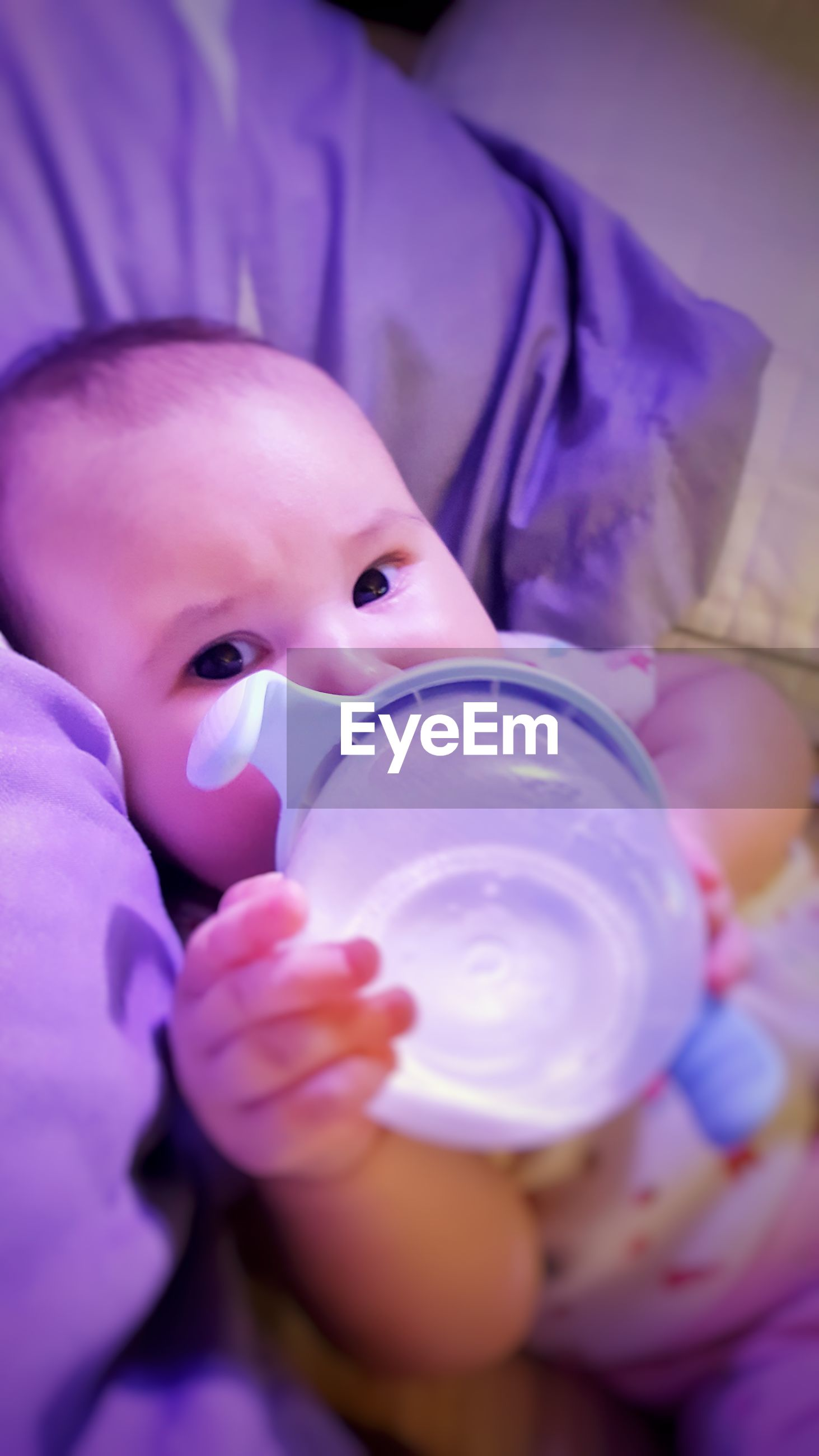 Close-up portrait of baby boy drinking milk while lying on bed at home