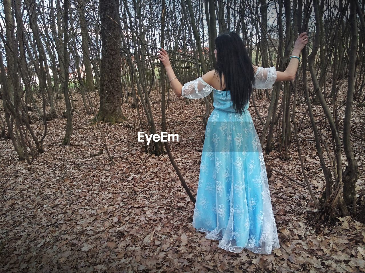 Woman wearing blue dress while standing in forest