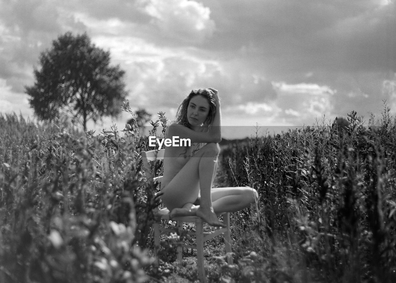 Portrait of naked woman sitting on bench at field against sky