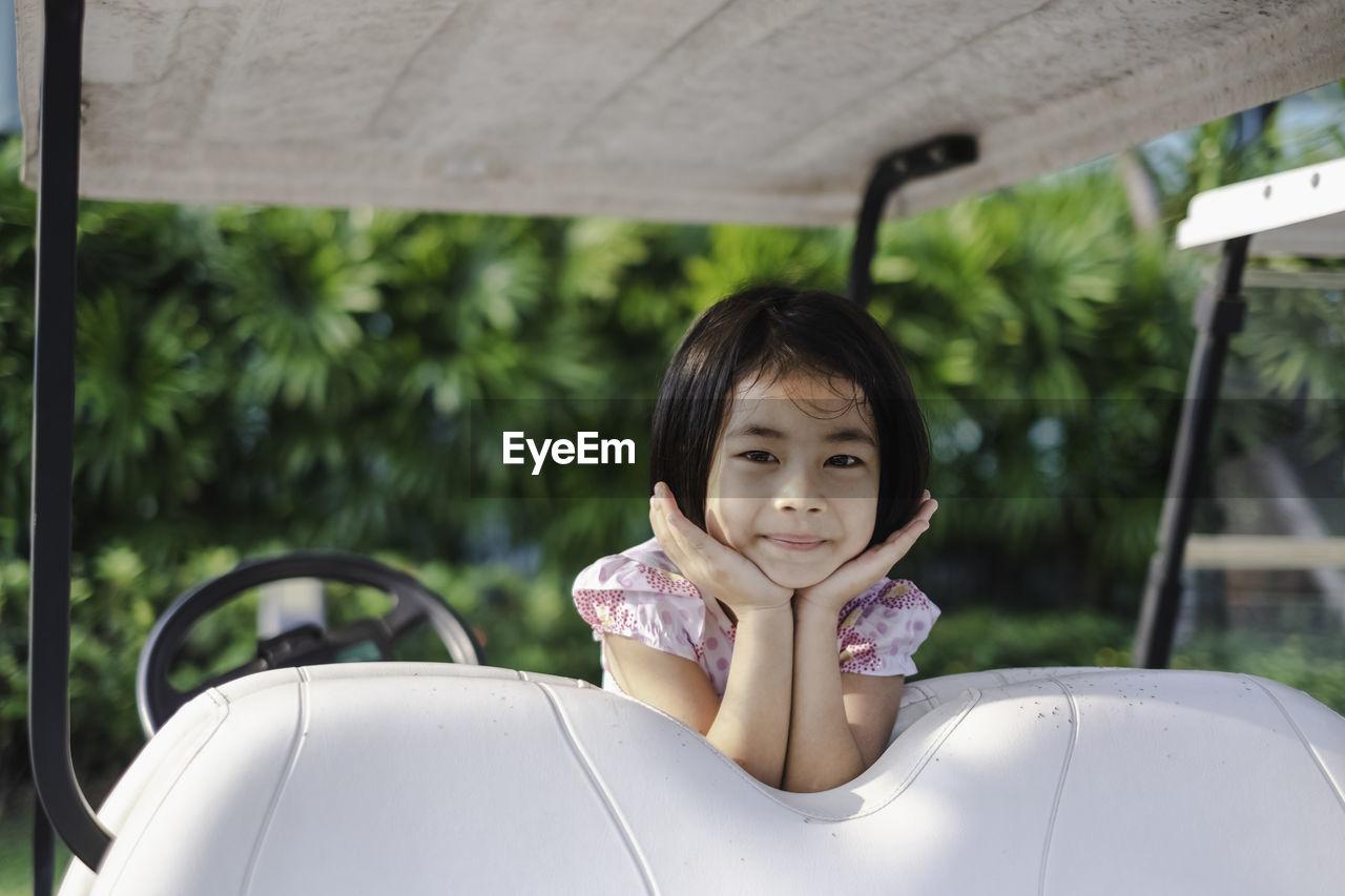 Portrait of smiling girl on golf cart