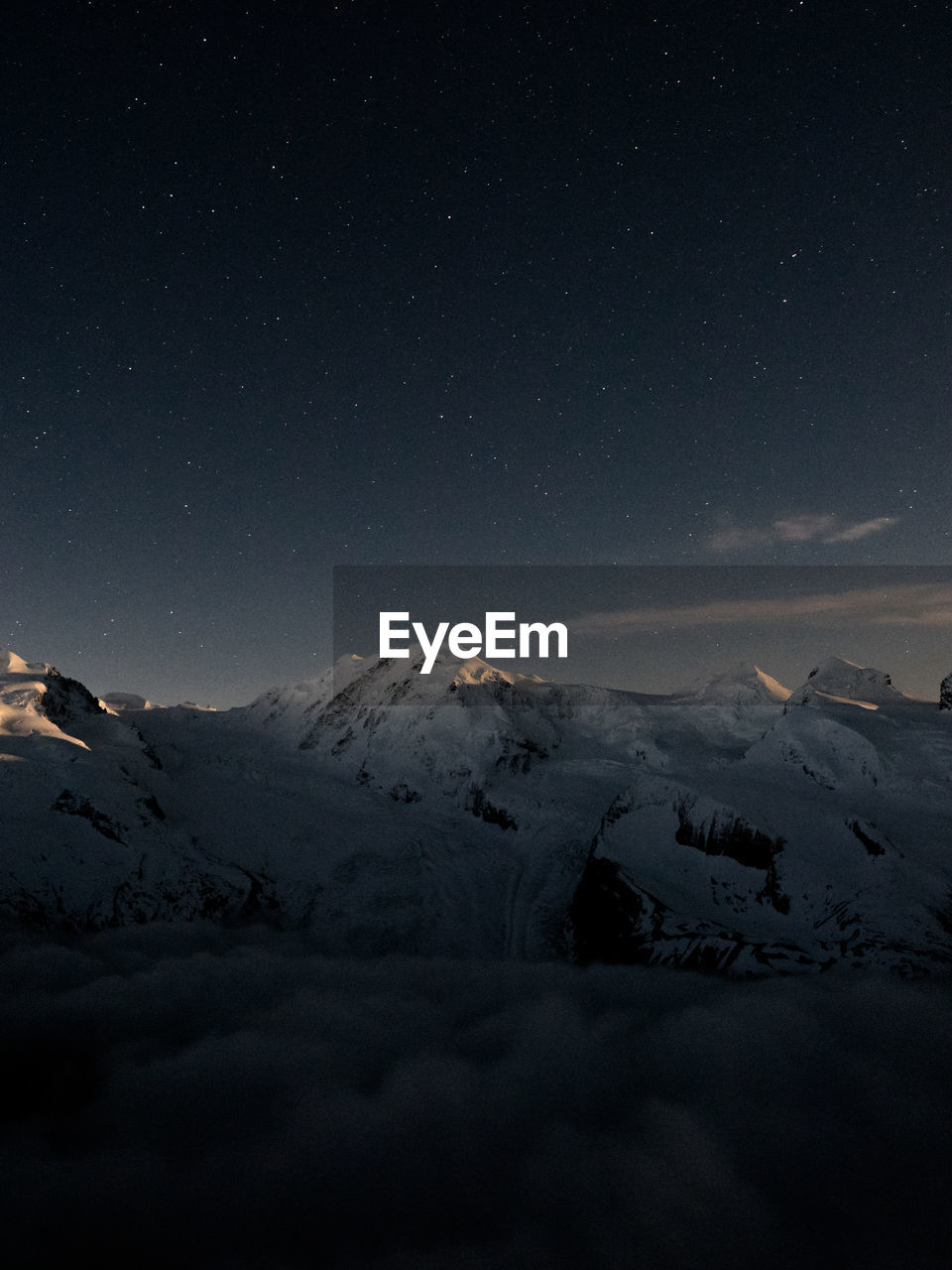Scenic view of snowy covered mountains against sky at night