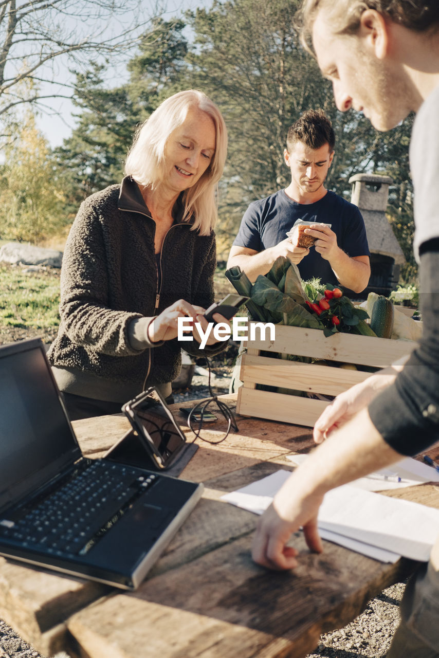 GROUP OF PEOPLE USING PHONE WHILE STANDING AT OUTDOOR