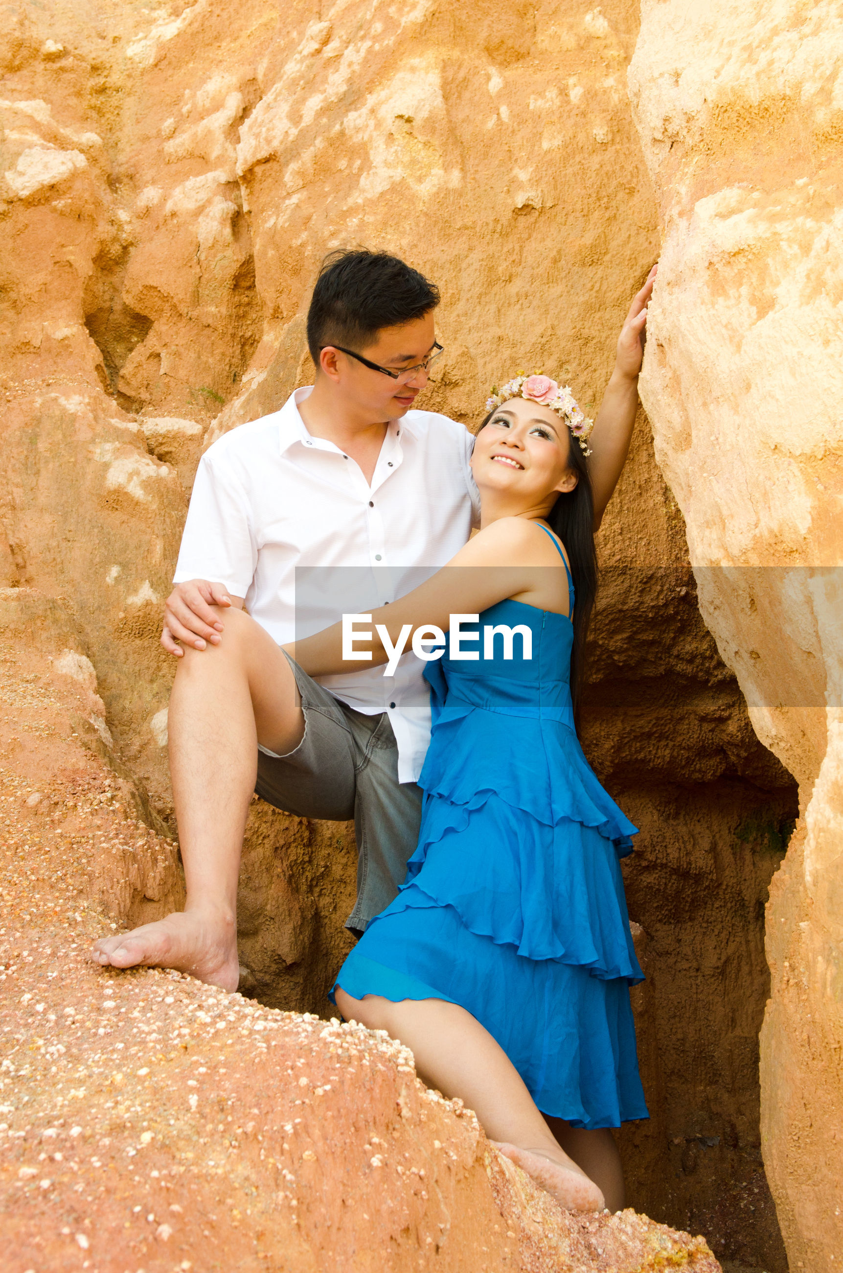 Woman embracing man while standing against rock formation