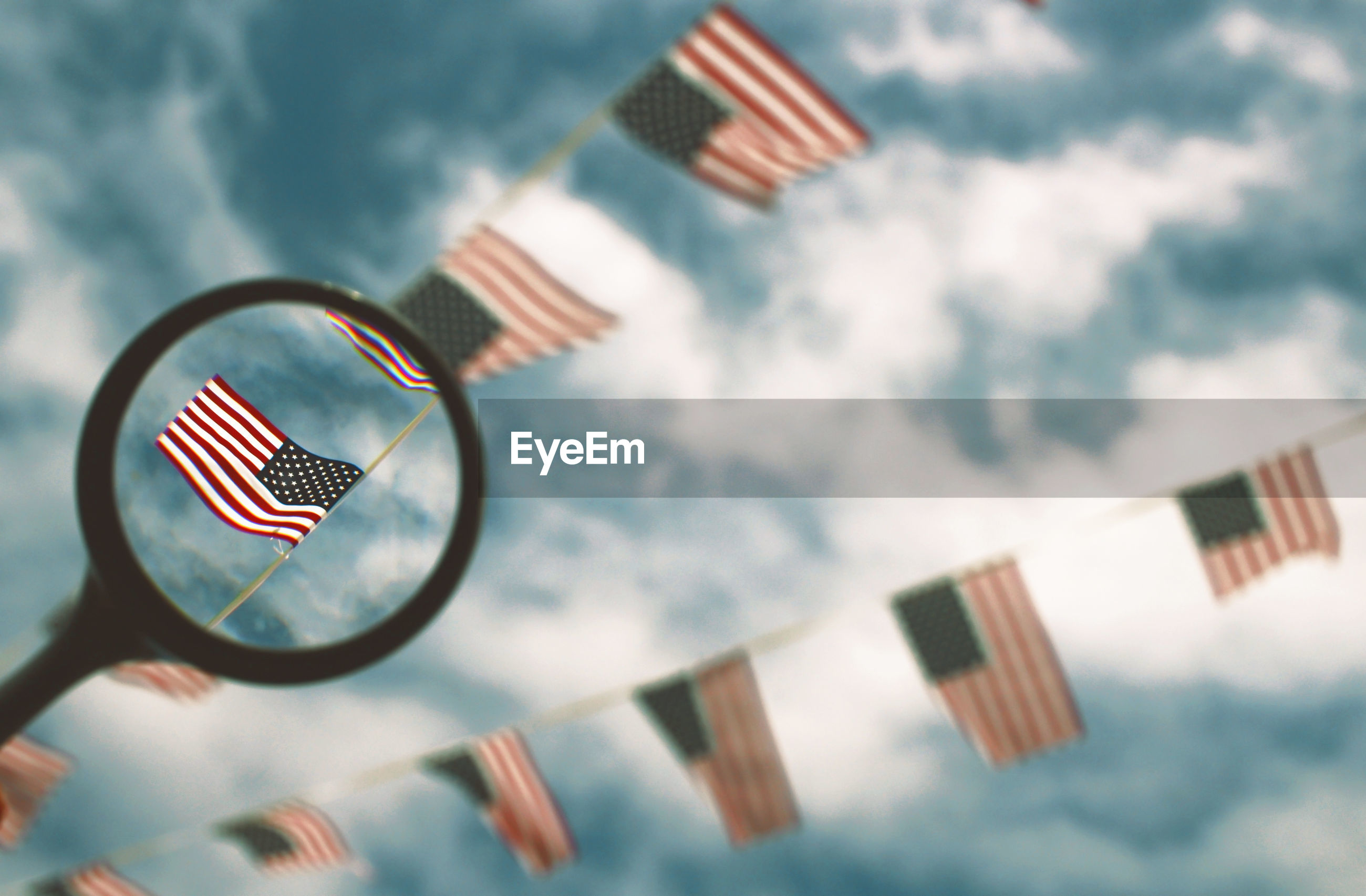 Low angle view of american flags seen through magnifying glass