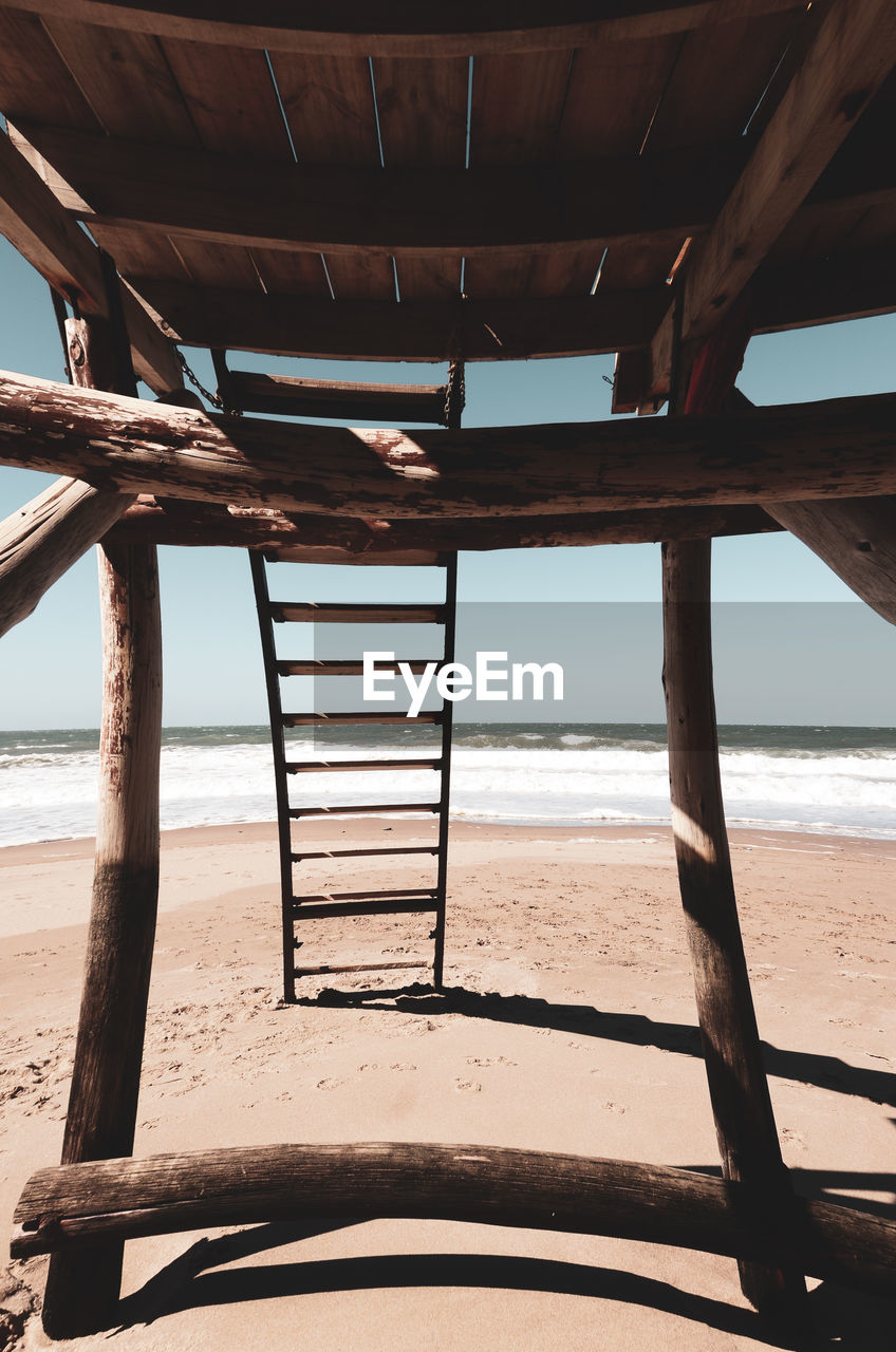 beach, water, sea, land, sand, sky, nature, horizon over water, day, horizon, architecture, beauty in nature, scenics - nature, wood - material, no people, tranquility, built structure, sunlight, tranquil scene, outdoors, ladder, underneath