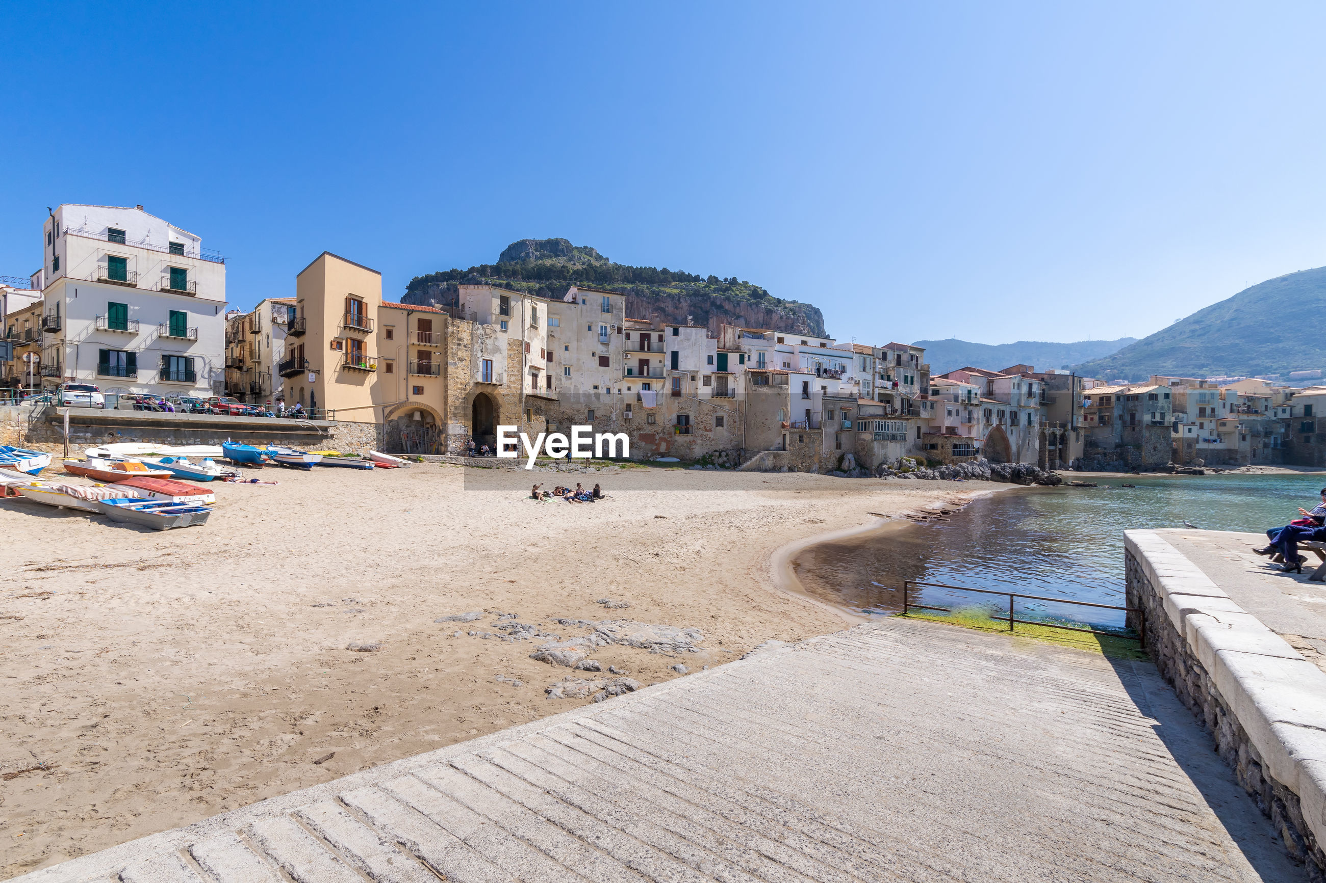 PANORAMIC VIEW OF BEACH BY BUILDINGS AGAINST CLEAR BLUE SKY