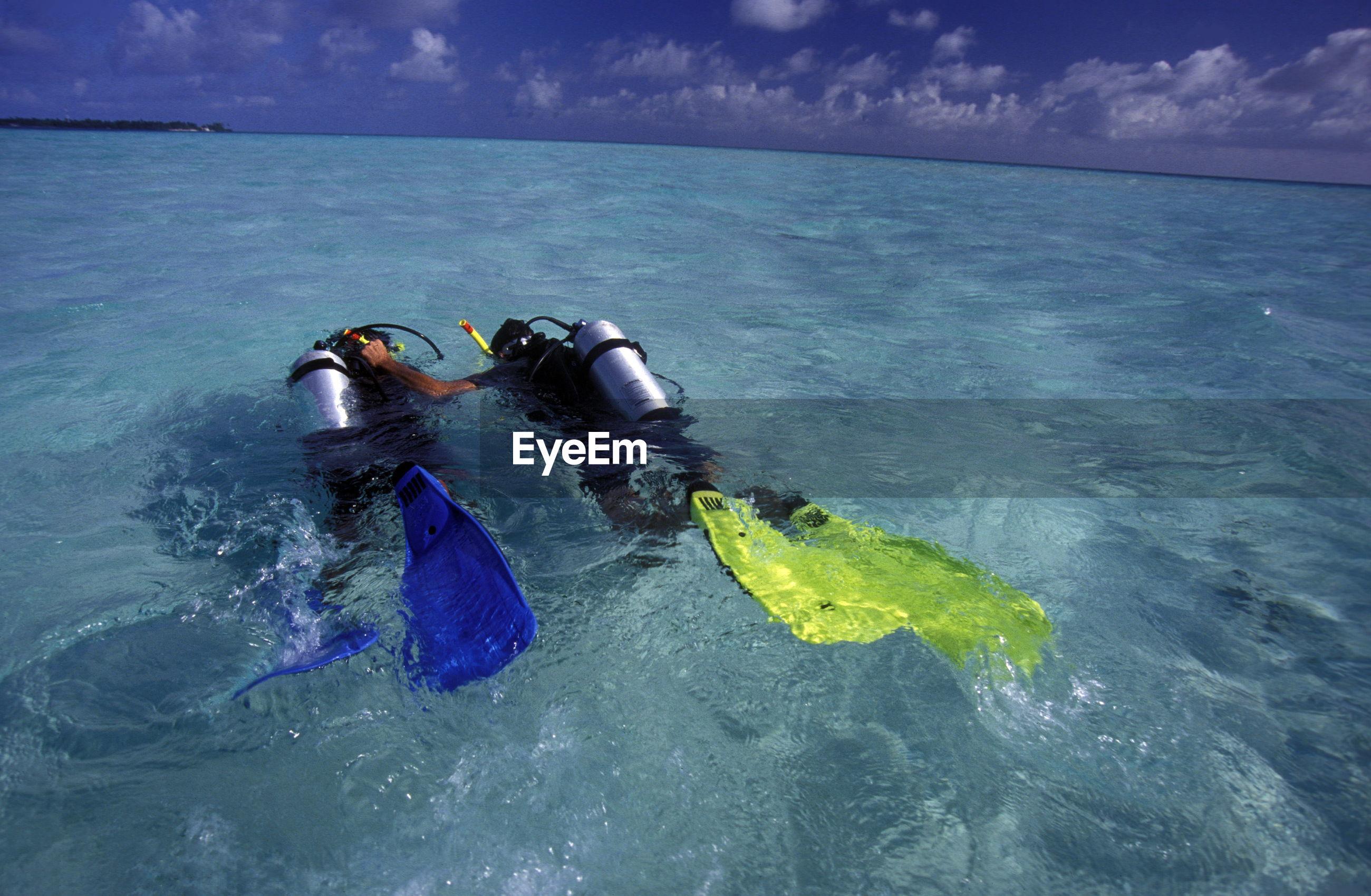 Scuba divers swimming in sea against sky
