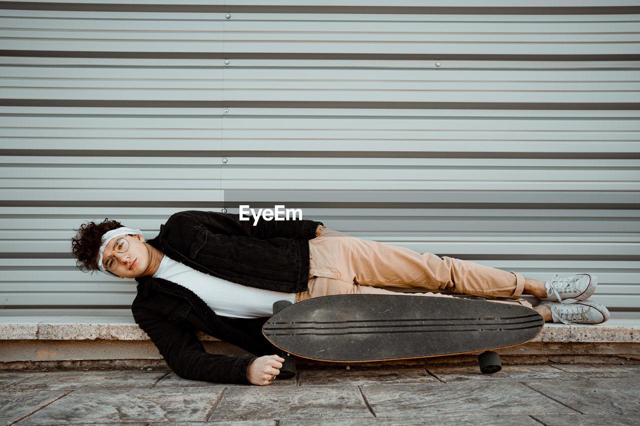 FULL LENGTH OF A MAN SLEEPING ON SHUTTER