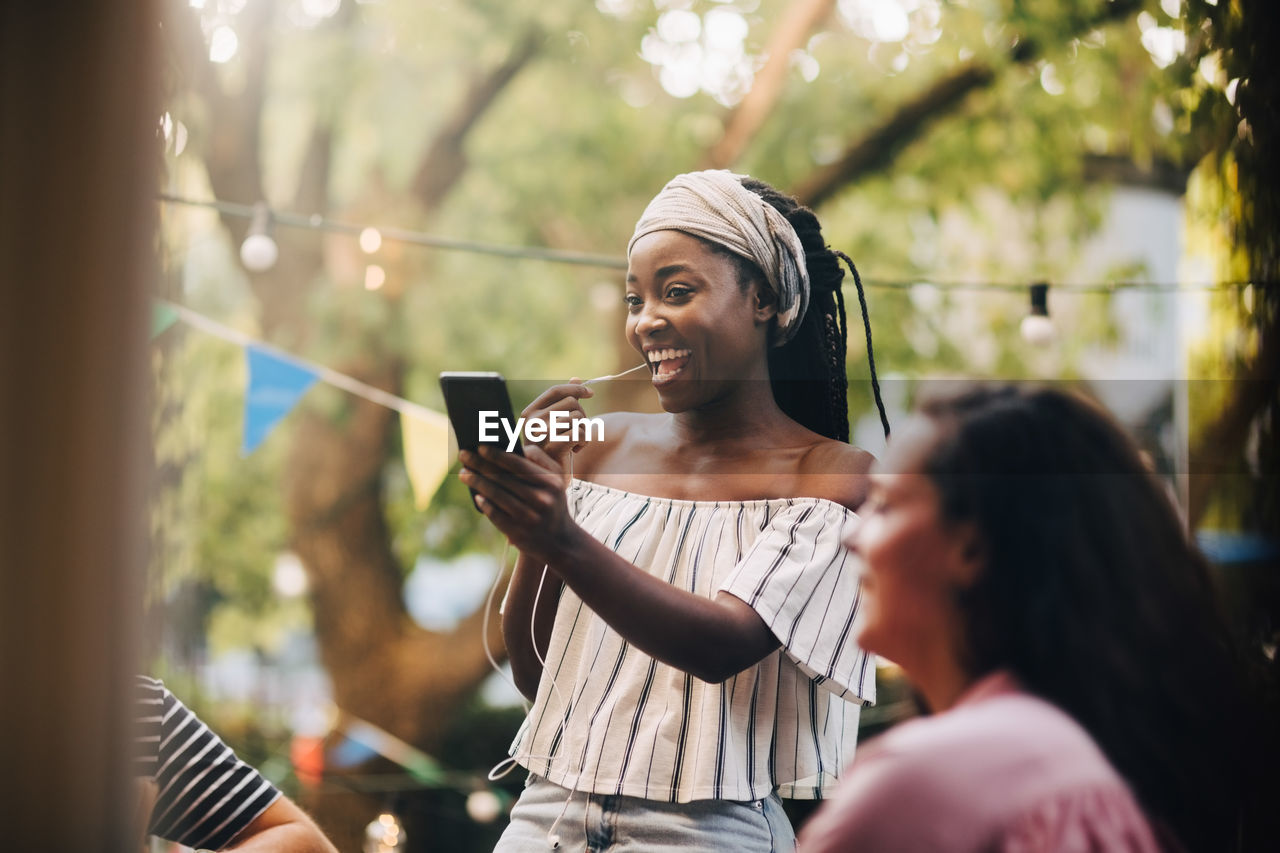 communication, wireless technology, technology, real people, smiling, portable information device, women, smart phone, happiness, mobile phone, adult, emotion, connection, lifestyles, young adult, young women, leisure activity, holding, two people, selective focus, outdoors
