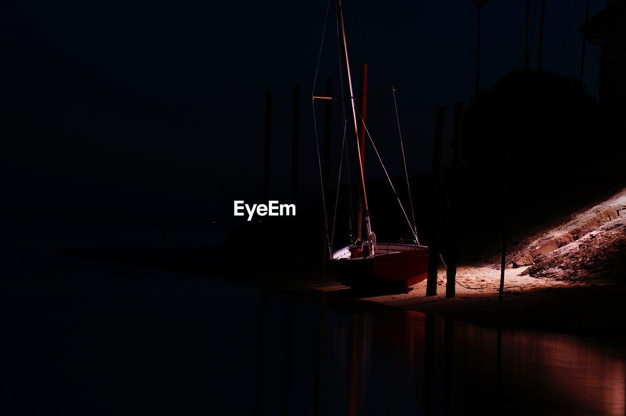 Sailboat Moored At Sea Shore During Night