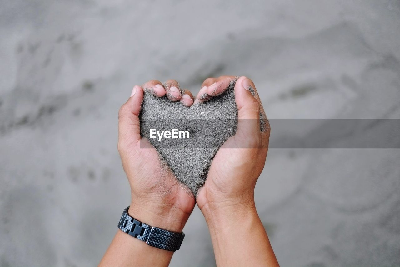 Close-up of hand holding sand with heart shape