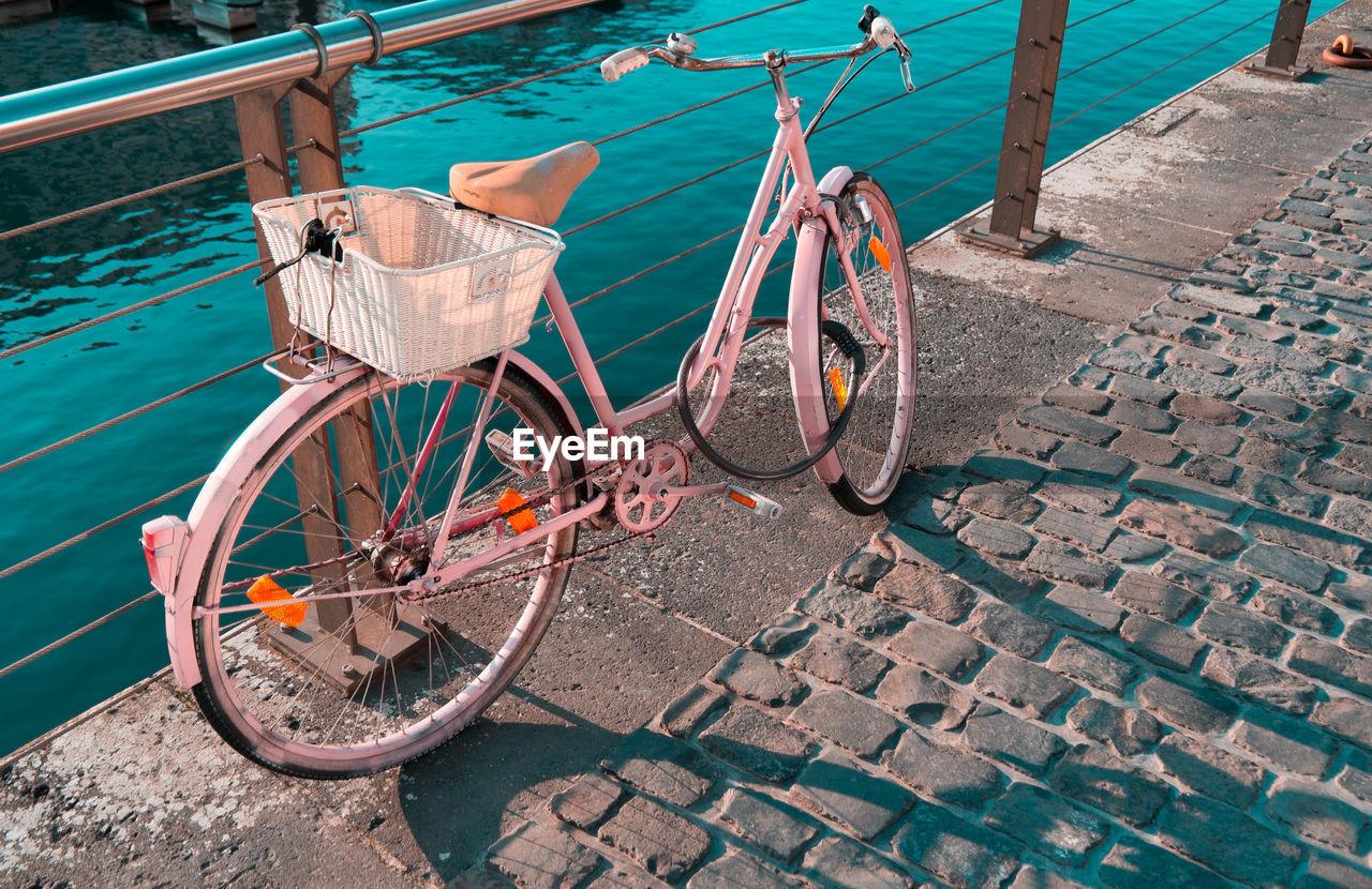 Pink Bicycle By River On Bridge