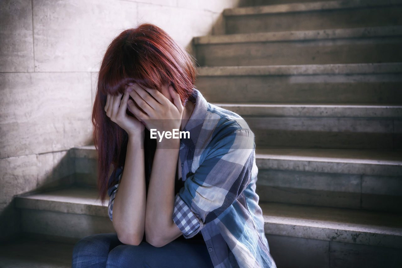 Depressed Girl Covering Face With Hands And Sitting On Steps