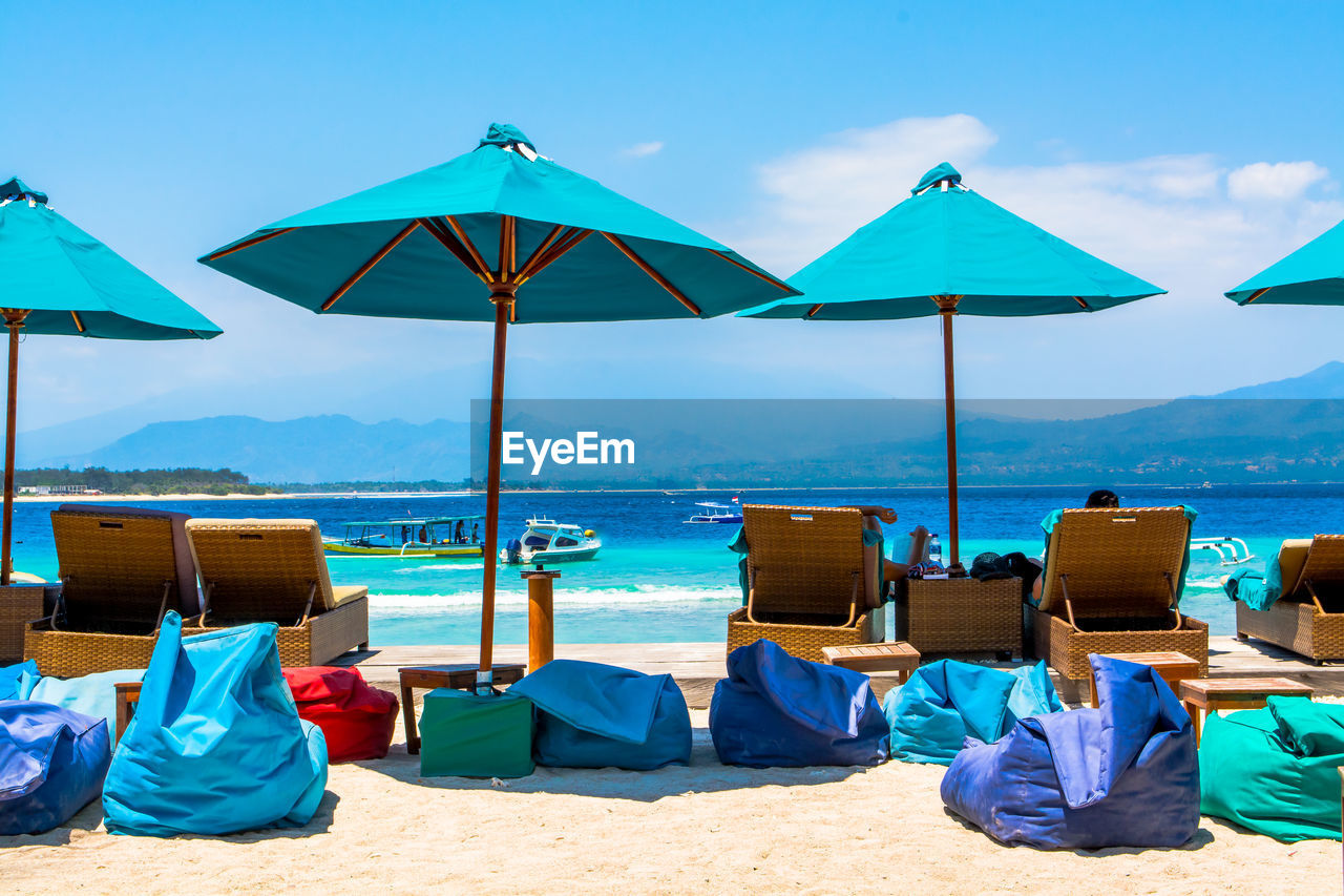 Parasols By Lounge Chairs And Bean Bags On Sand At Beach Against Sky