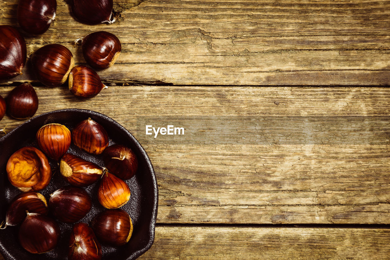 wood - material, food and drink, food, brown, table, directly above, still life, indoors, healthy eating, freshness, no people, nut, wellbeing, nut - food, high angle view, chestnut, large group of objects, textured, close-up, chestnut - food, snack, wood grain