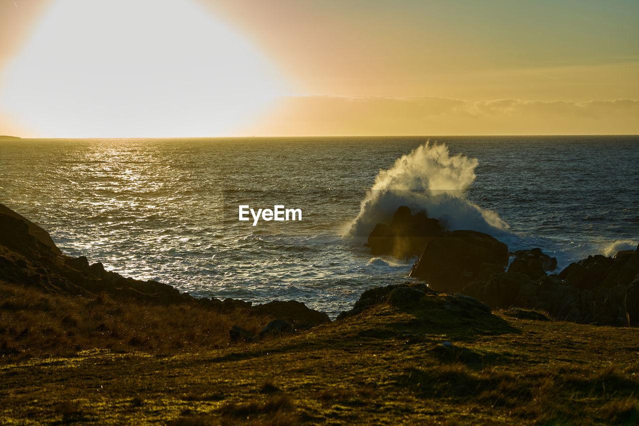 SEA WAVES SPLASHING ON ROCKS AT SUNSET