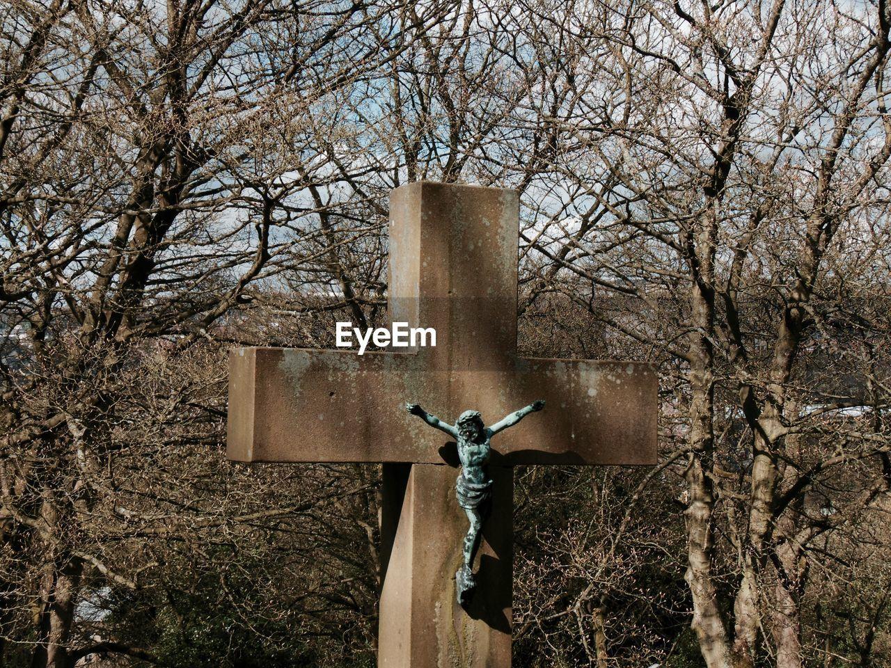 Crucifix against bare trees