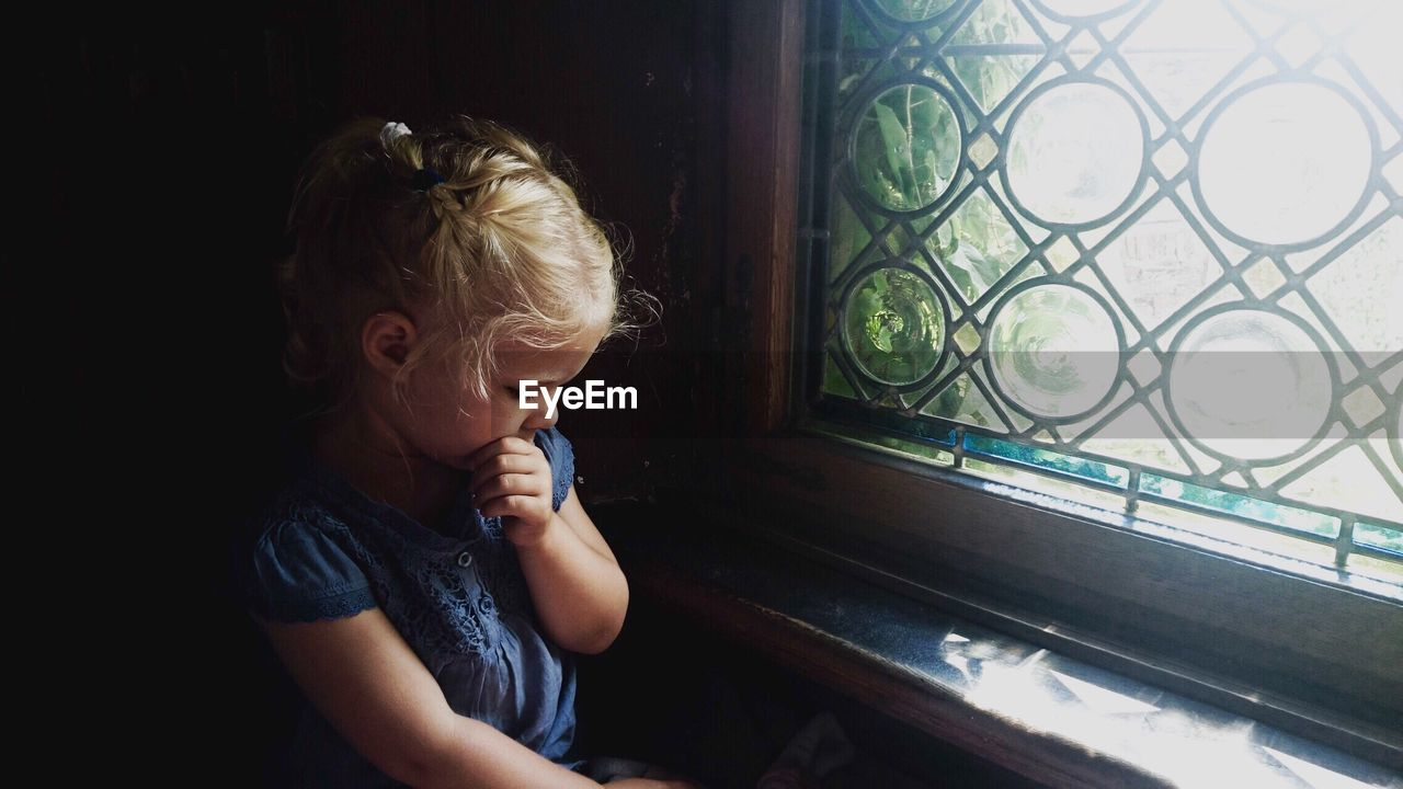 Sad Girl Sitting By Window At Home