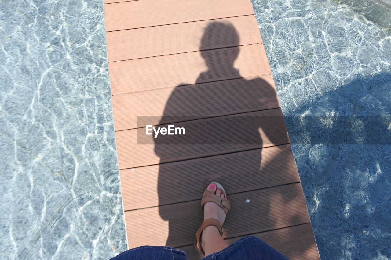 low section, human leg, real people, human body part, pool, swimming pool, body part, personal perspective, one person, water, shadow, sunlight, nature, shoe, human foot, high angle view, lifestyles, leisure activity, day, outdoors, slipper, at the edge of, tiled floor