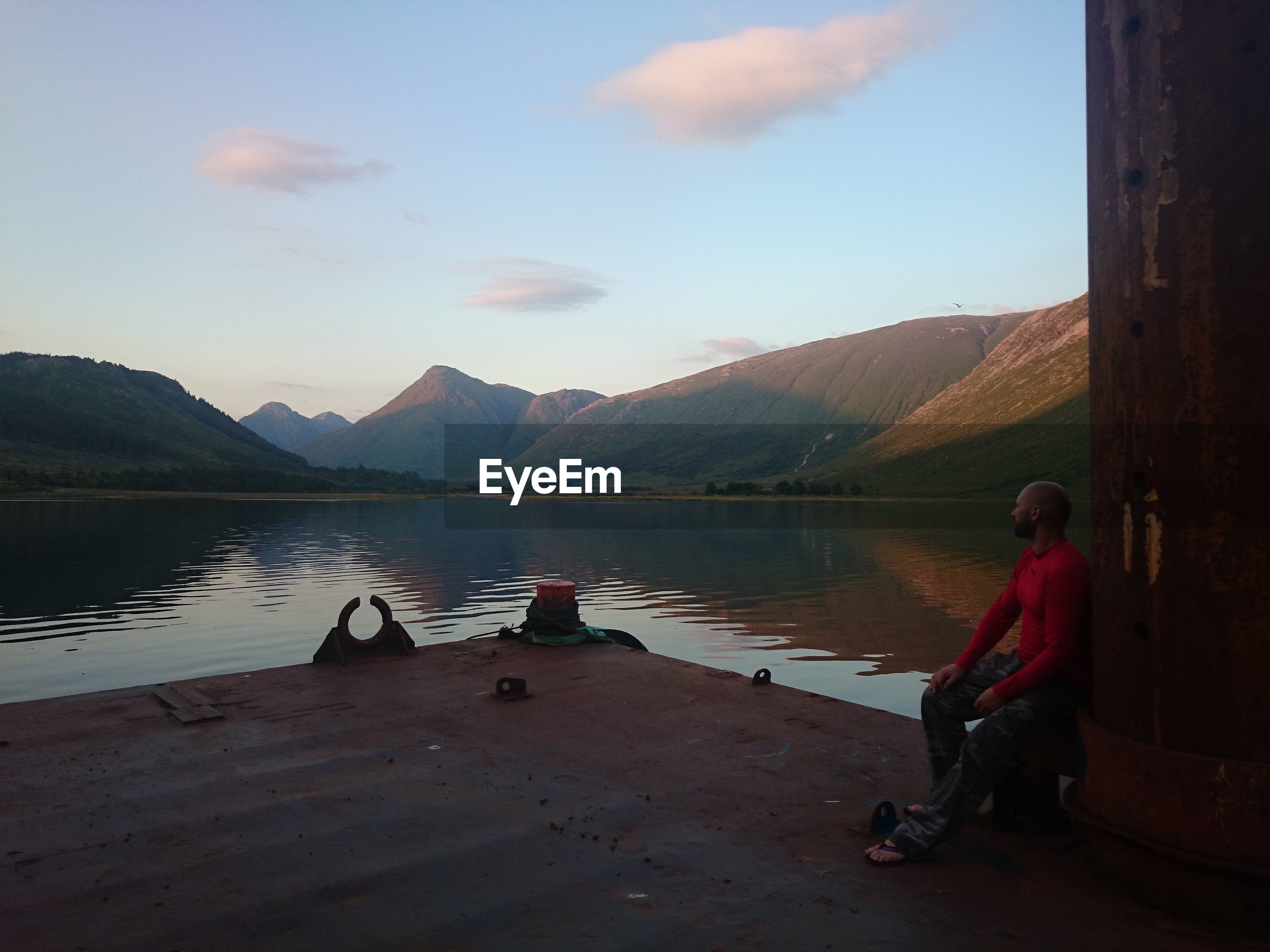 mountain, water, leisure activity, lake, lifestyles, rear view, full length, mountain range, casual clothing, sitting, sky, men, standing, nautical vessel, nature, tranquility, beauty in nature, scenics