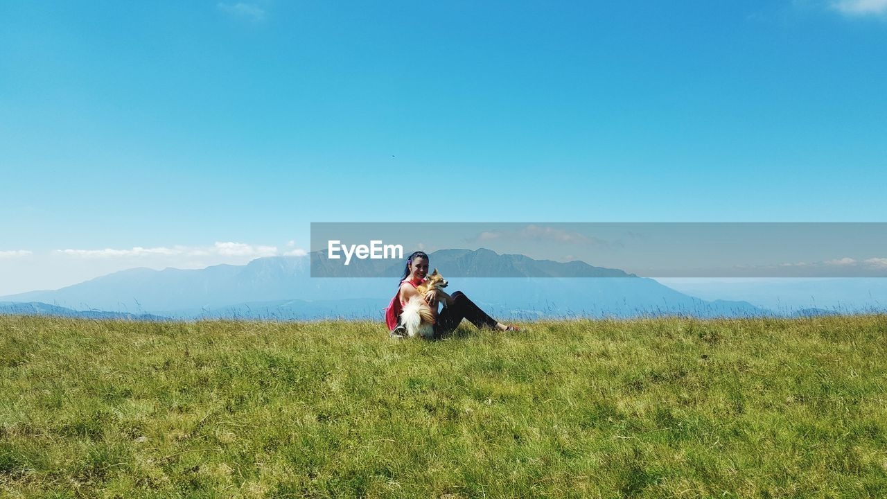 Woman Sitting With Dog On Grassy Field Against Blue Sky