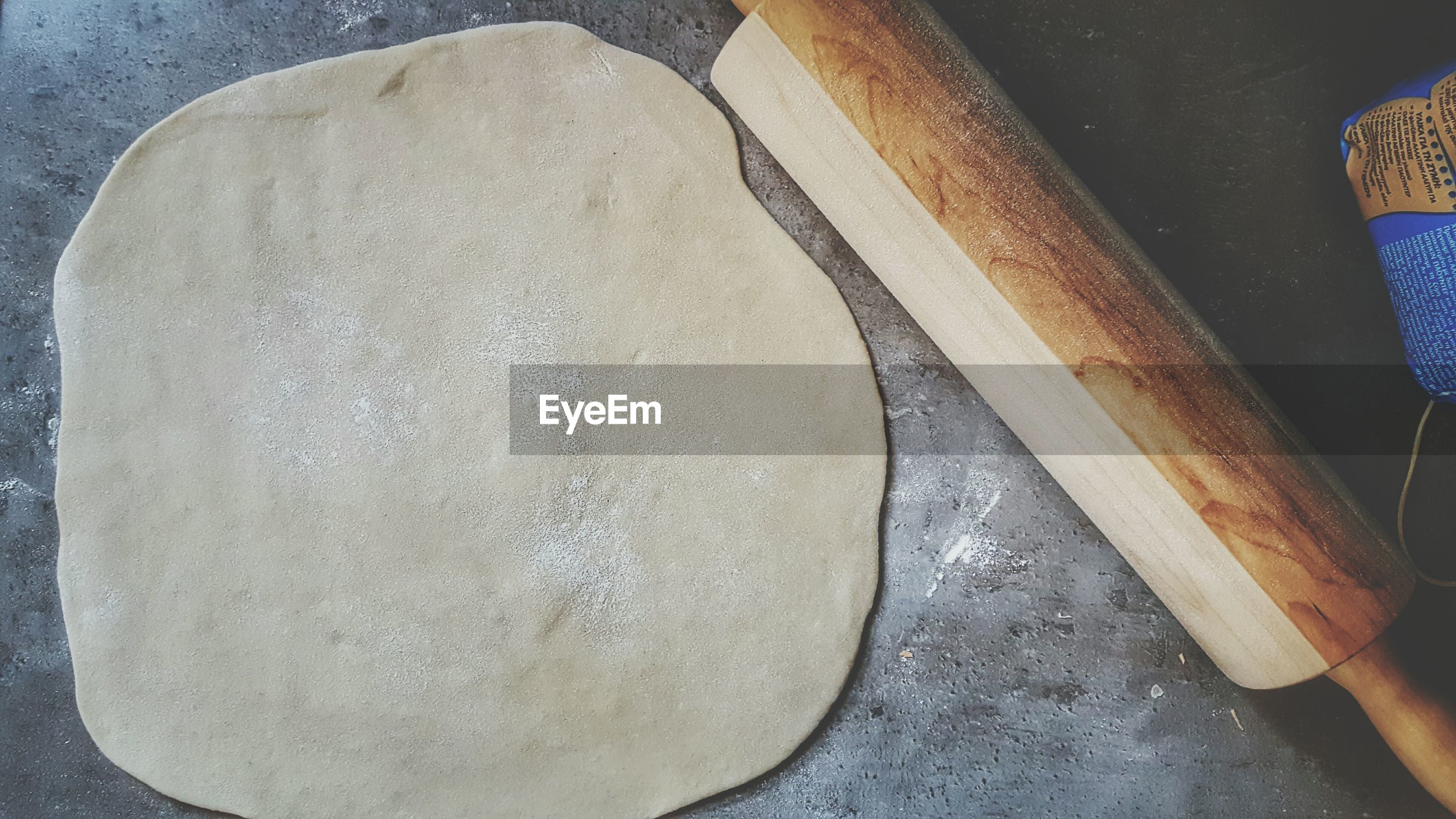 High angle view of dough by rolling pin on table