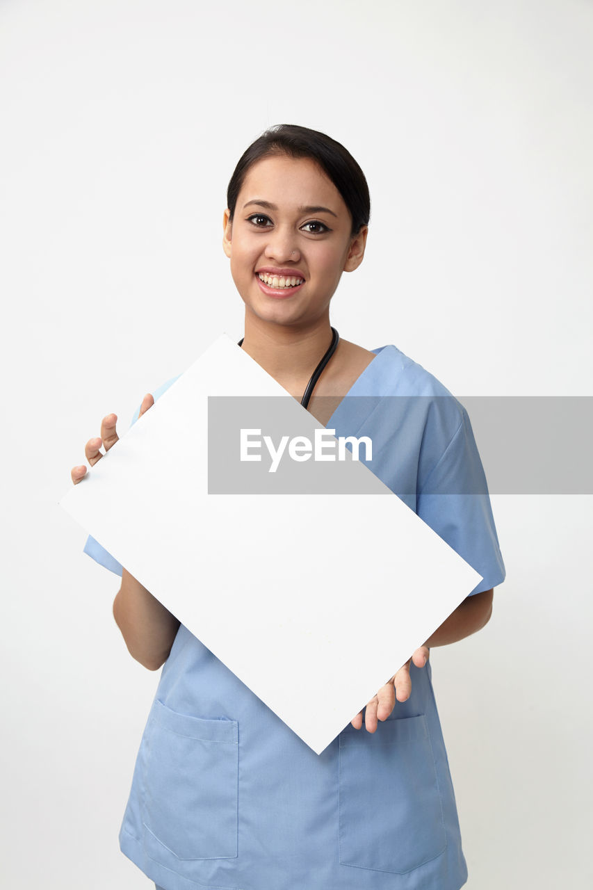 Portrait of smiling female doctor holding blank placard against white background