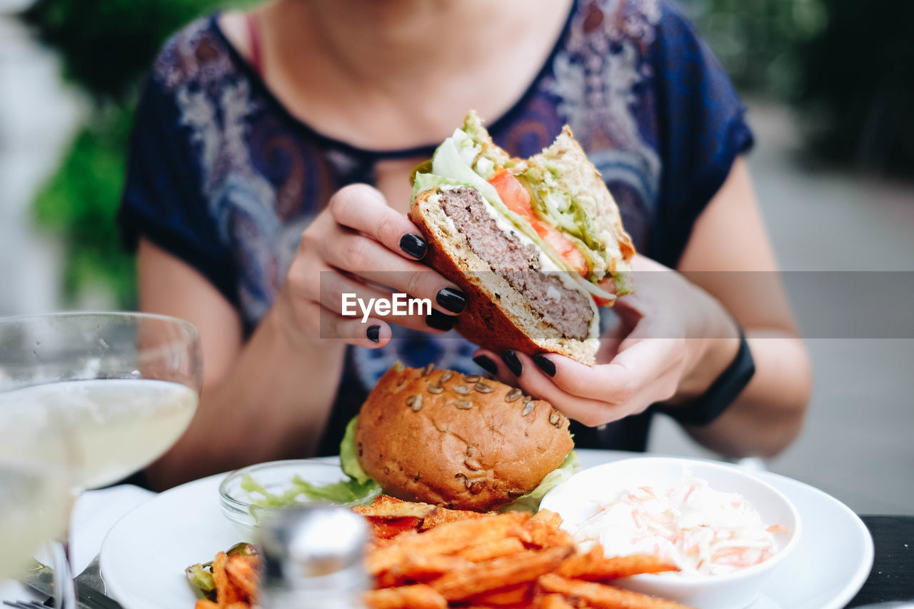 Midsection Of Woman Holding Having Burger At Restaurant