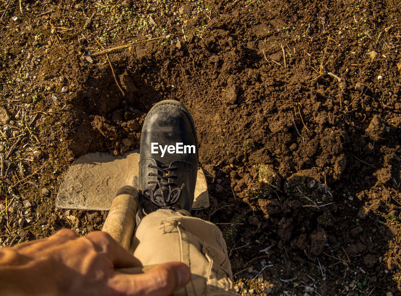 real people, one person, low section, land, nature, day, human body part, high angle view, men, shoe, human leg, body part, lifestyles, relaxation, personal perspective, casual clothing, solid, field, rock, outdoors