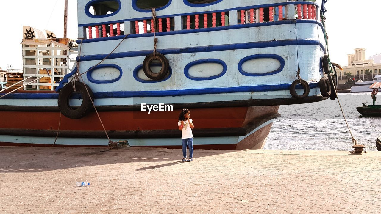 built structure, real people, architecture, building exterior, day, one person, leisure activity, outdoors, full length, standing, lifestyles, nautical vessel, water, city, young adult