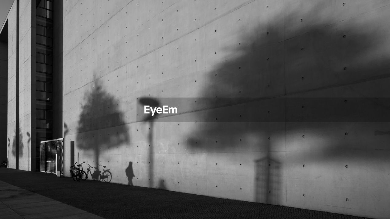 architecture, built structure, building exterior, wall - building feature, shadow, building, nature, day, city, glass - material, window, outdoors, sunlight, no people, transparent, walking, wall, motion, blurred motion, focus on shadow