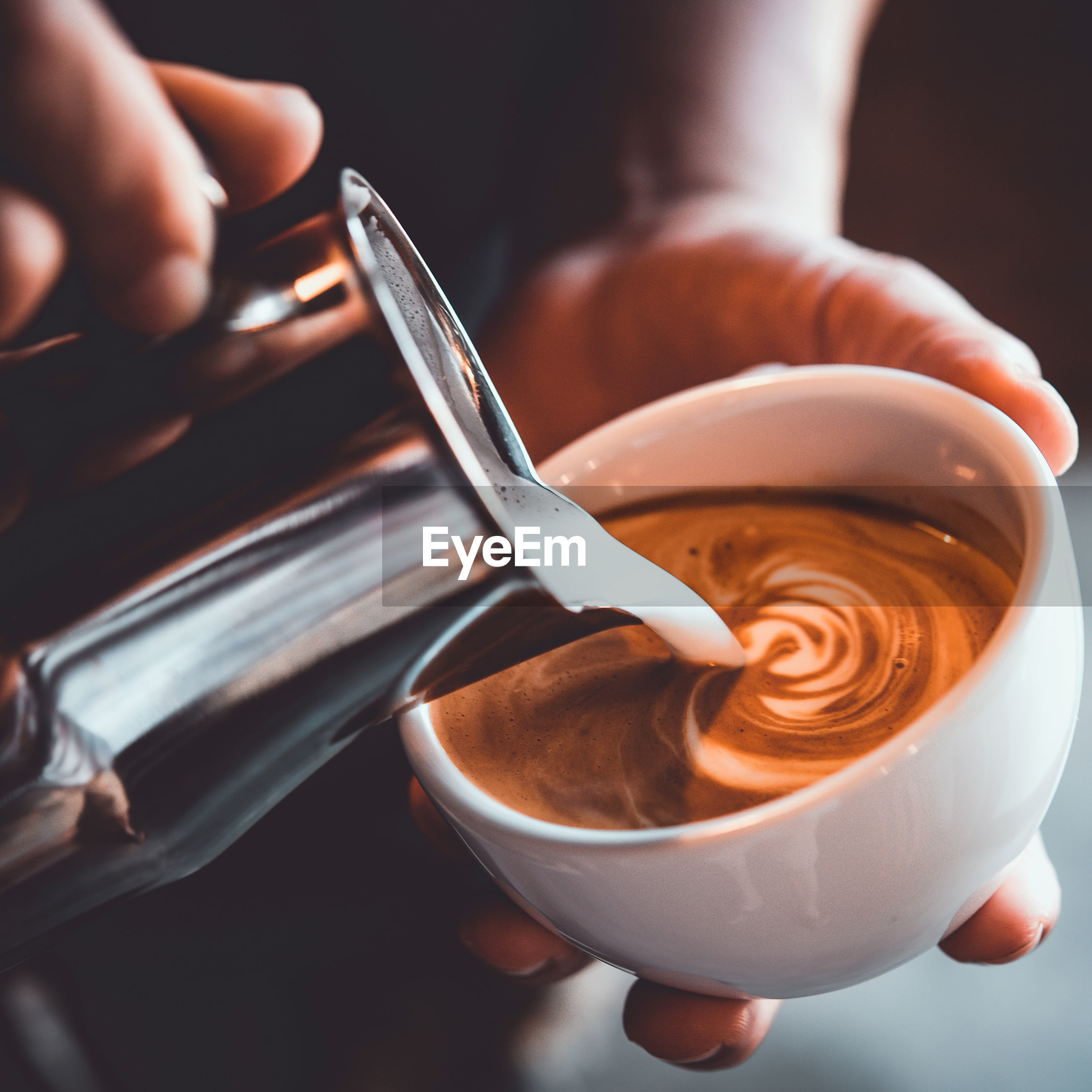 Midsection of person pouring milk in coffee cup