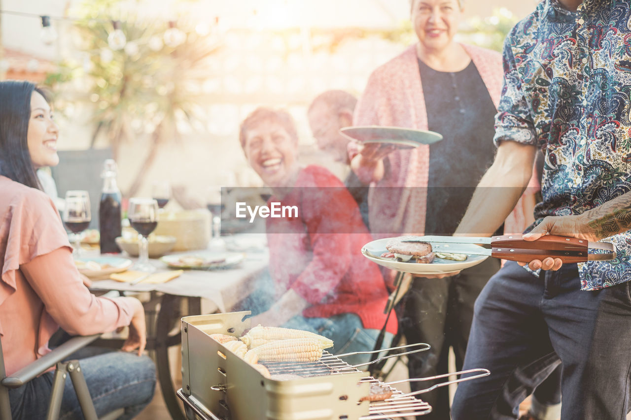 group of people, men, real people, barbecue grill, preparation, food and drink, lifestyles, women, adult, barbecue, day, standing, food, leisure activity, casual clothing, meat, people, medium group of people, smoke - physical structure, group, preparing food, outdoors