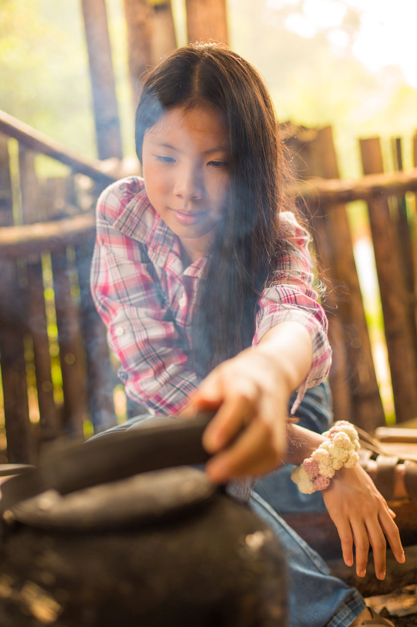 Young Woman Cooking Outdoors
