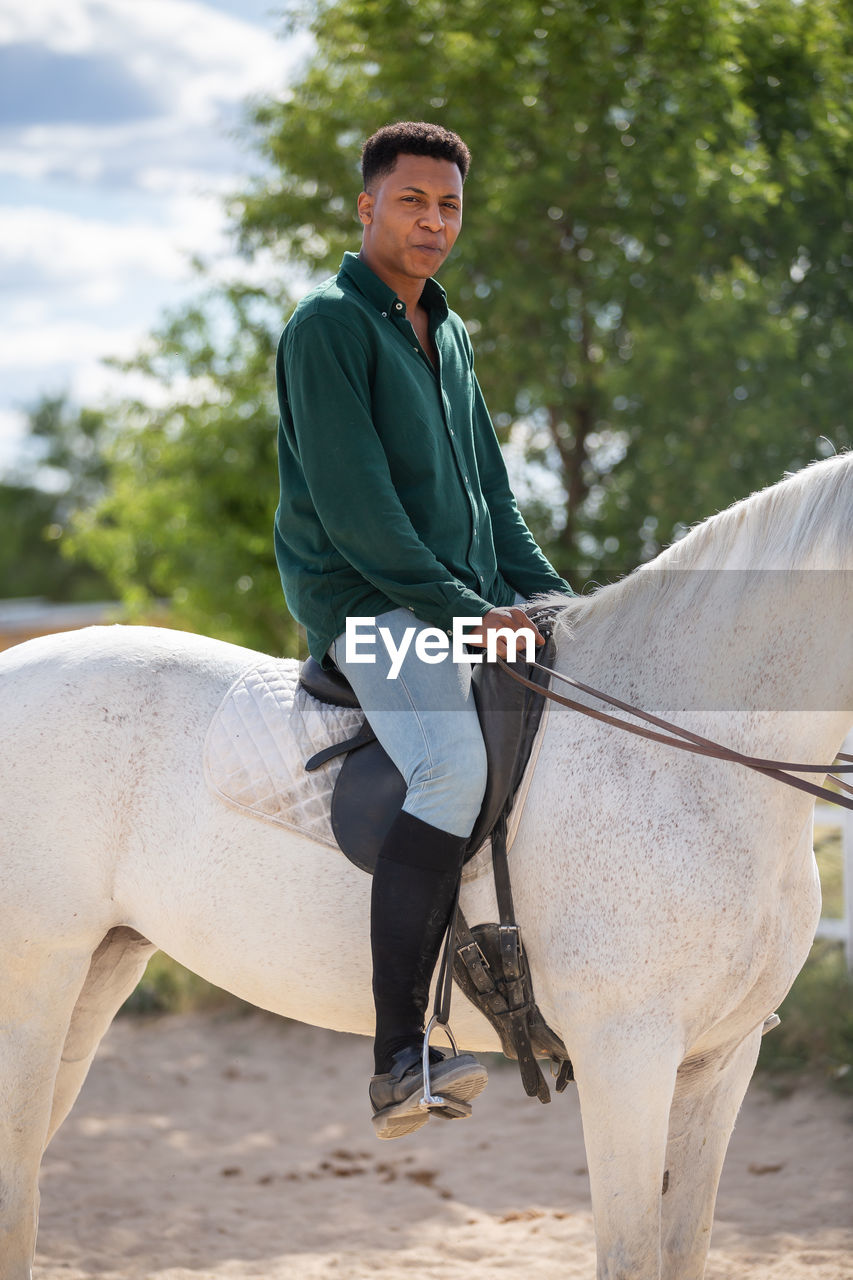 FULL LENGTH PORTRAIT OF YOUNG WOMAN RIDING HORSE