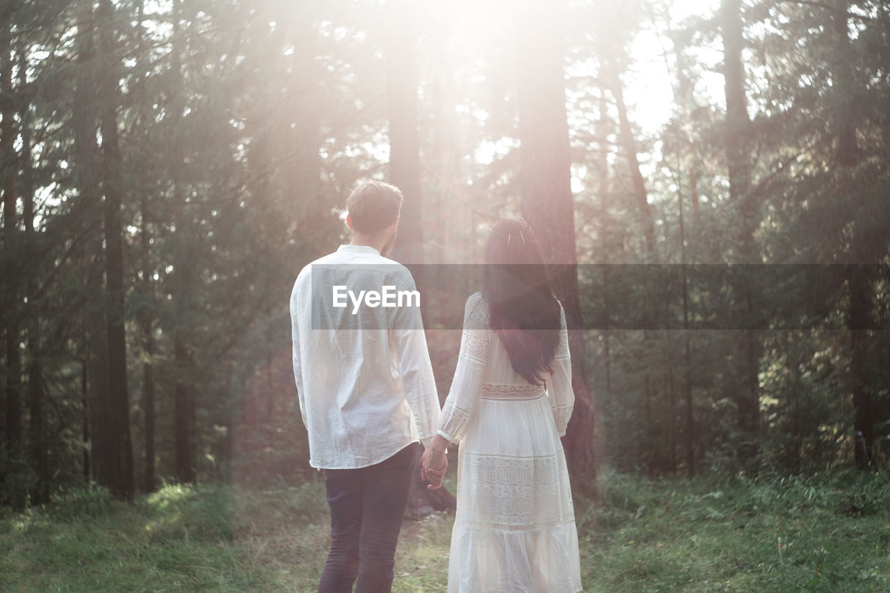 two people, togetherness, land, tree, forest, three quarter length, plant, standing, nature, young men, women, casual clothing, young adult, men, real people, couple - relationship, day, leisure activity, young women, love, woodland, outdoors, positive emotion