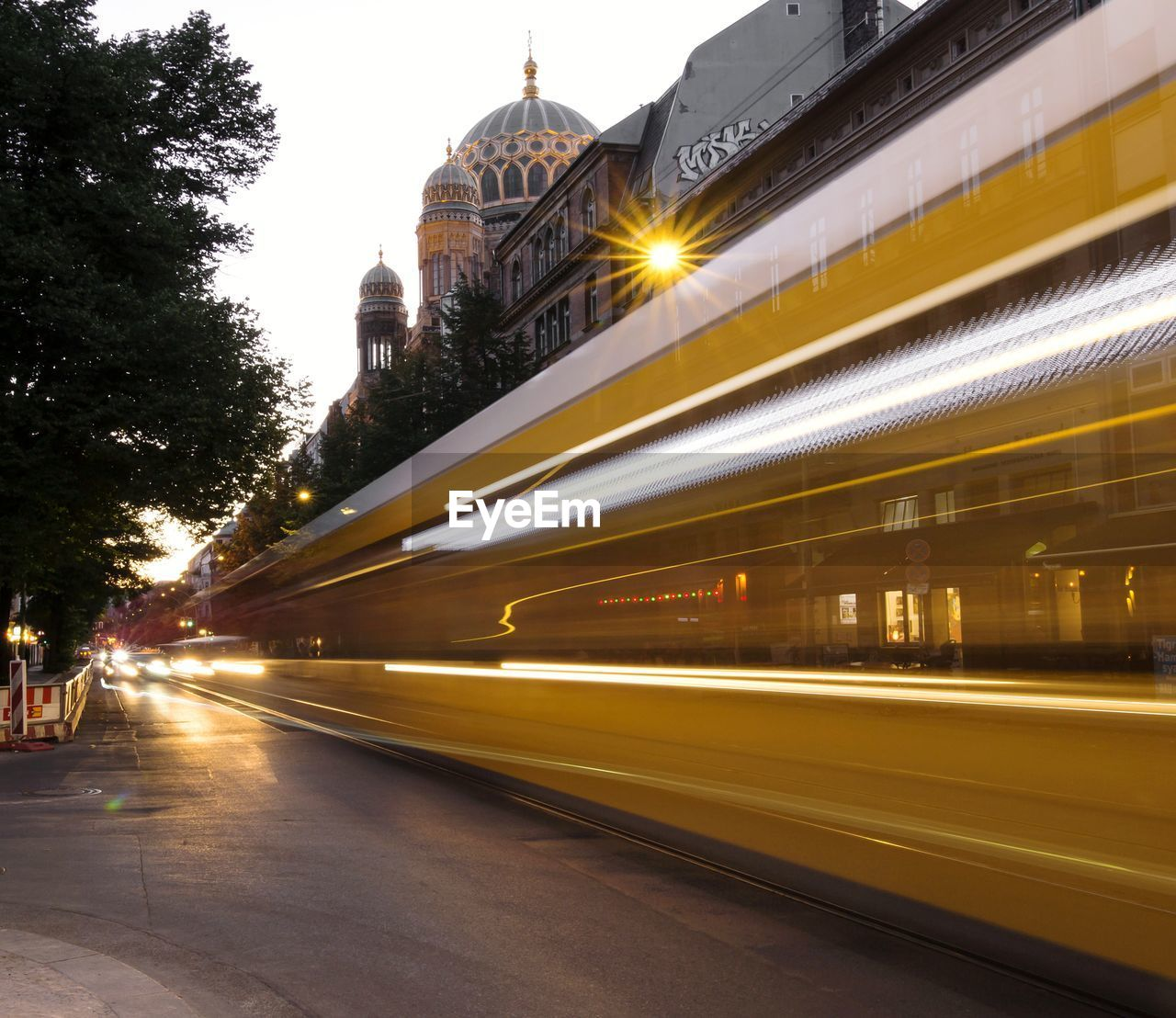 LIGHT TRAILS ON STREET IN CITY AGAINST SKY IN BACKGROUND
