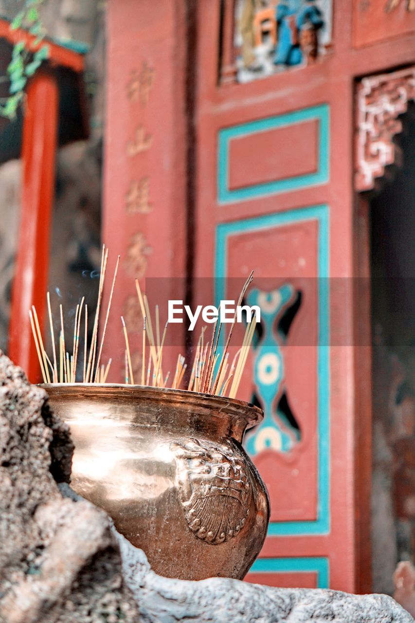 place of worship, incense, belief, religion, architecture, spirituality, built structure, no people, focus on foreground, red, close-up, building, day, art and craft, outdoors, script, container, non-western script, selective focus, shrine