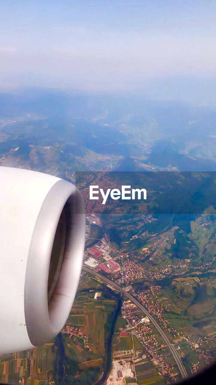 aerial view, airplane, air vehicle, transportation, flying, mid-air, journey, travel, no people, aircraft wing, mode of transport, jet engine, landscape, day, outdoors, scenics, patchwork landscape, sky, nature, airplane wing, city