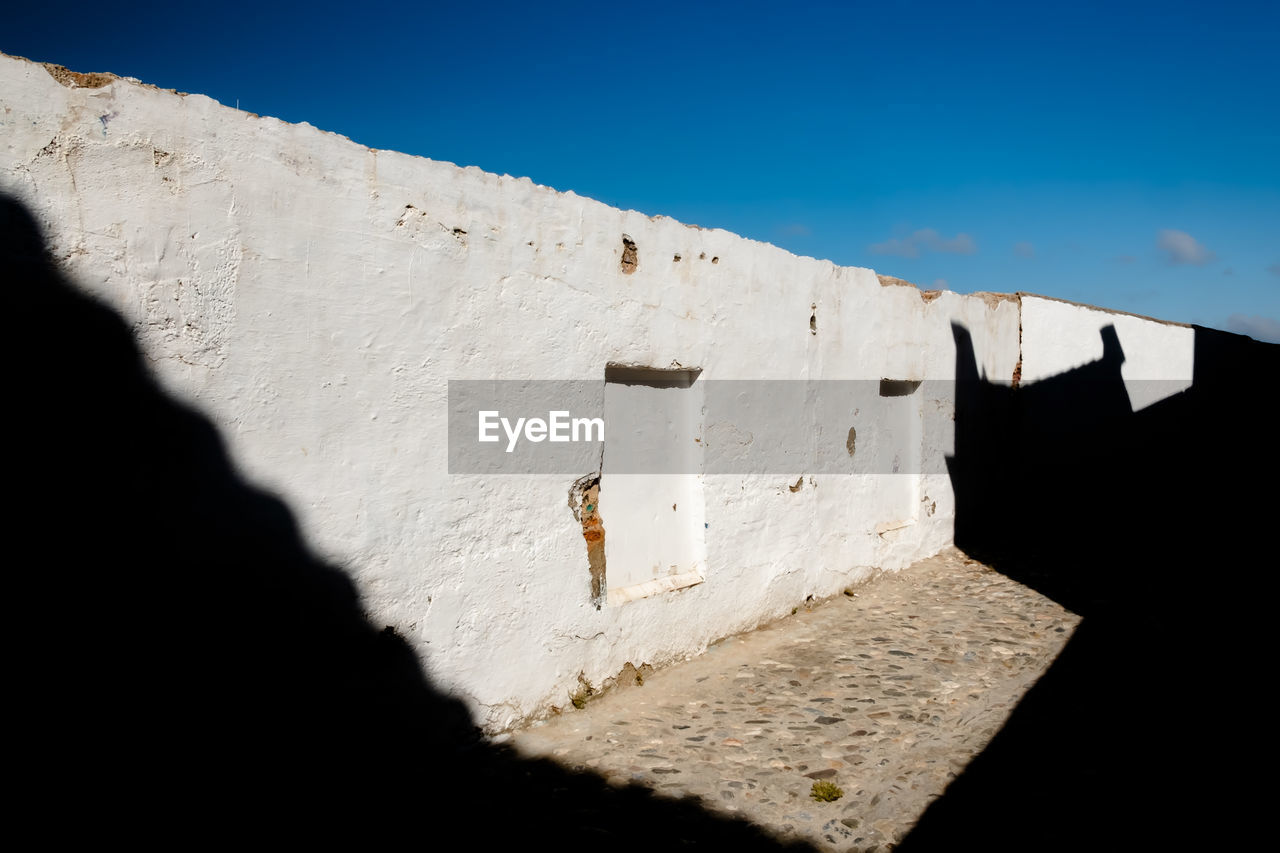 sunlight, shadow, nature, architecture, wall - building feature, built structure, blue, wall, day, sky, outdoors, no people, old, clear sky, close-up, building exterior, copy space, white color, history, low angle view, concrete