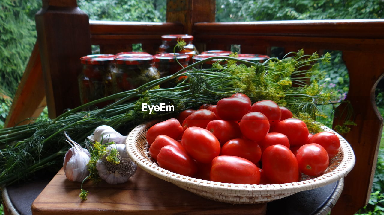 Close-Up Of Tomatoes In Bowl By Jars And Herbs On Table